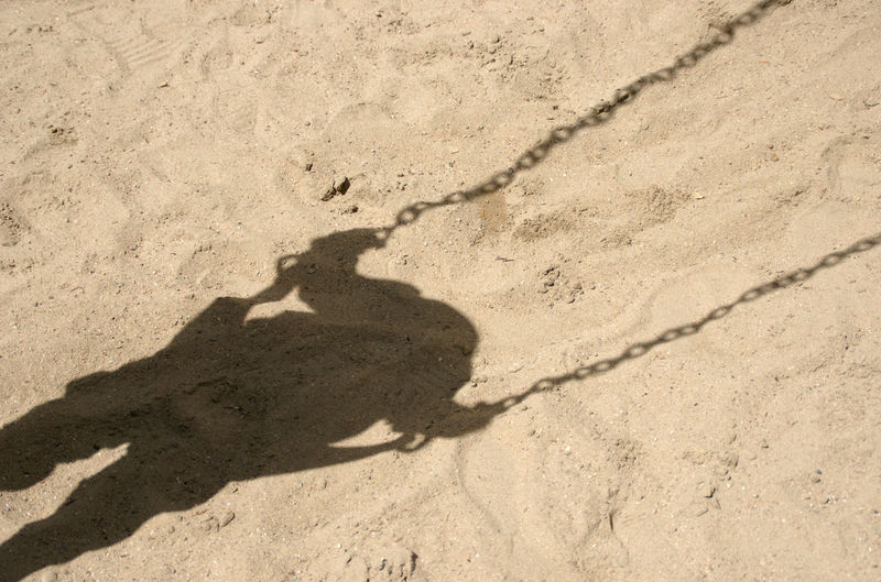 Shadow of a child sitting on a swing Adult Adults Only Beach Day Focus On Shadow Human Body Part Human Hand Men One Man Only One Person Only Men Outdoors People Sand Shadow Silhouette Spielen, Play Sunlight Swing, Child, Childhood, Playground, Swining, Schaukel, Kind, Schaukeln, Kindheit