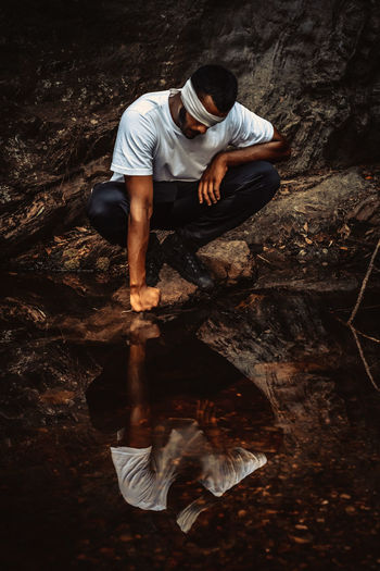 Full length of man with blindfold crouching by river