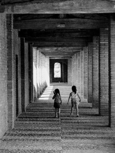 Friends Walking In Corridor Of Building