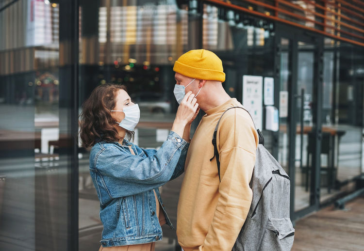 Stylish young family couple hipsters in face mask against glass building, new normal