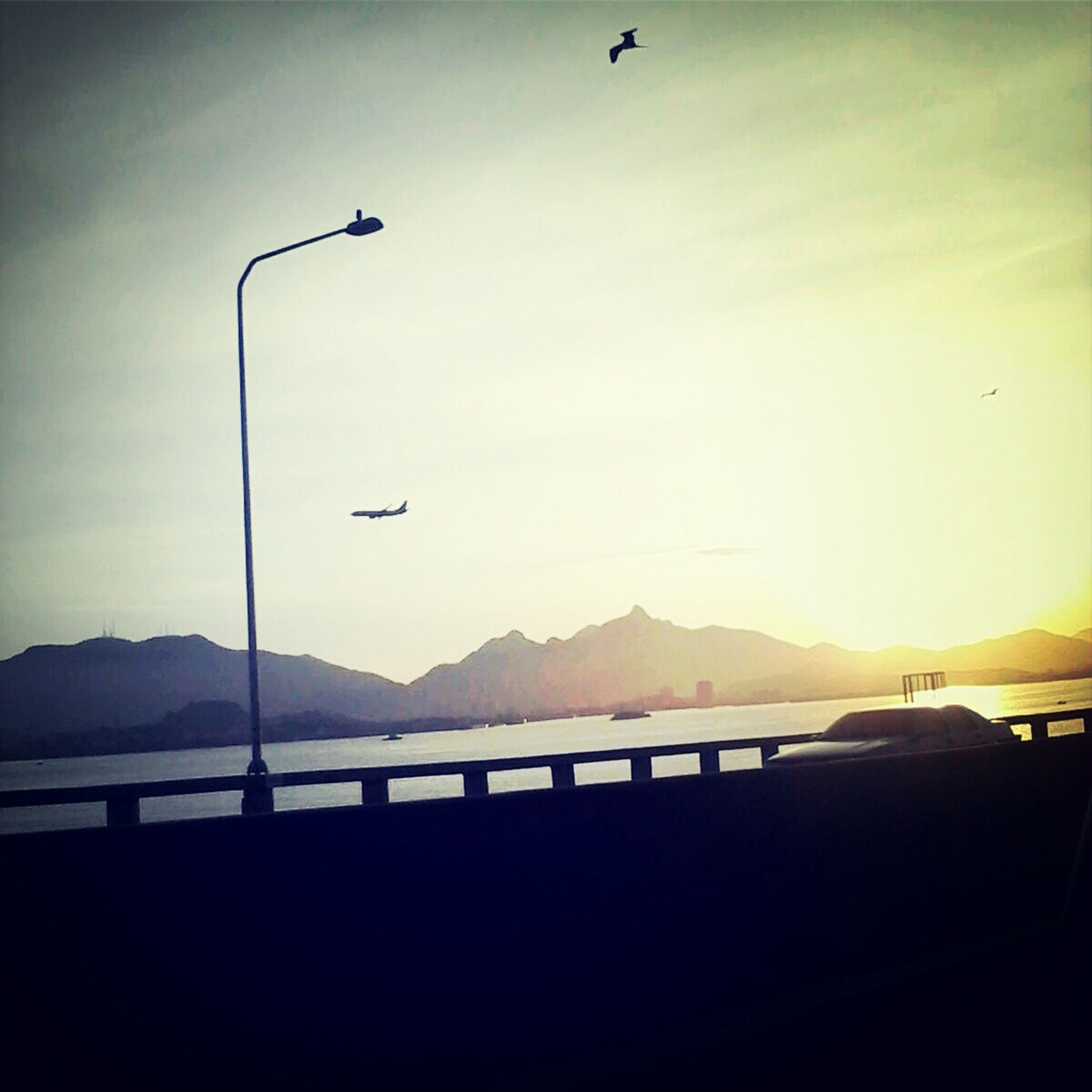 mountain, mountain range, silhouette, sky, transportation, sunset, scenics, tranquility, street light, nature, beauty in nature, landscape, tranquil scene, railing, road, flying, clear sky, outdoors, copy space, no people