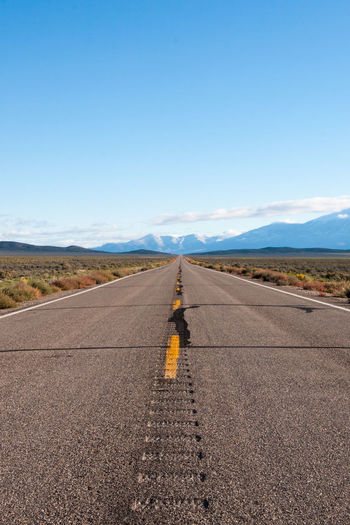 Long, Straight Road, Nevada Asphalt Blue Clear Sky Day Diminishing Perspective Empty Road Highway Landscape Long Straight Road Nature Nevada No People Outdoors Road Road Trip Sky Snow Capped Mountains The Way Forward The Way Foward Transportation Two Lane Highway USA Vertical