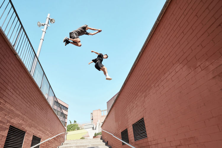Low angle view of men jumping against clear sky