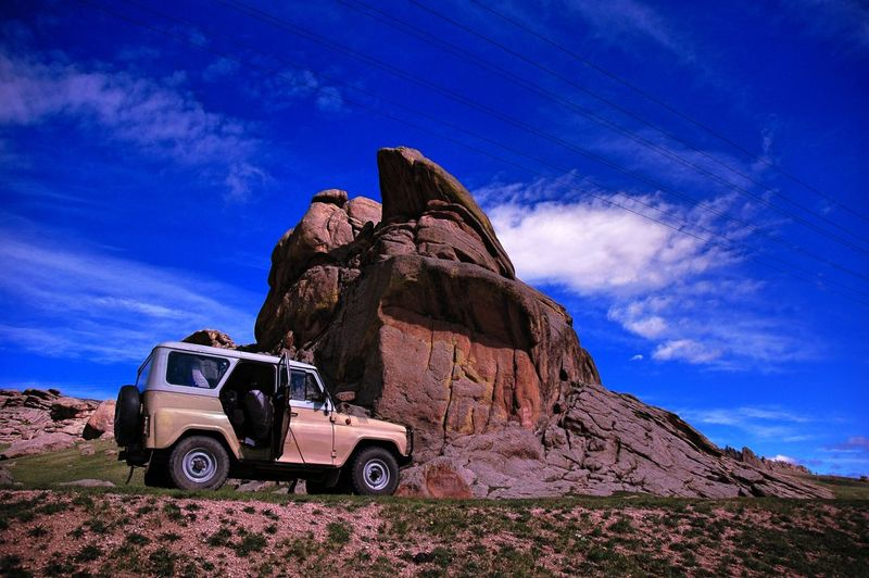 Off-Road Vehicle By Rock Formation Against Sky
