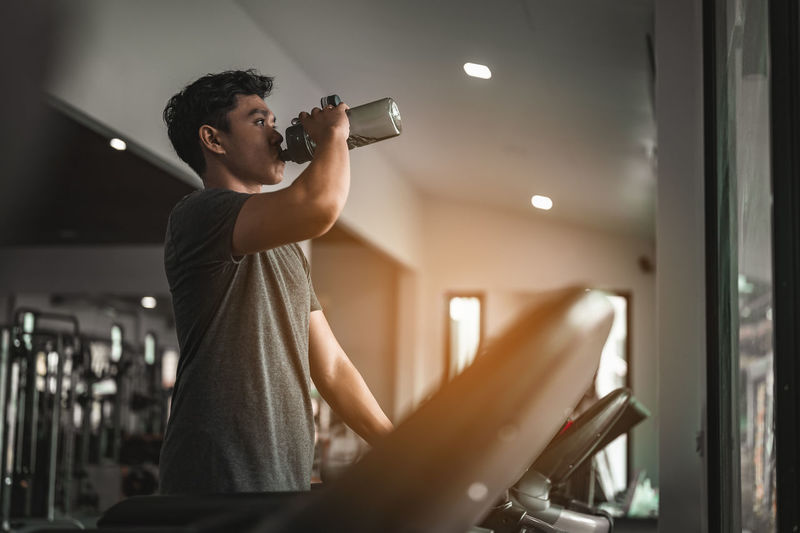 Young man drinking water while exercising in gym