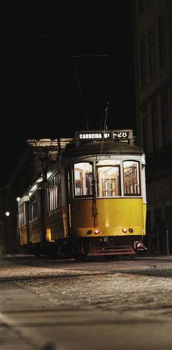 Train on illuminated street in city at night
