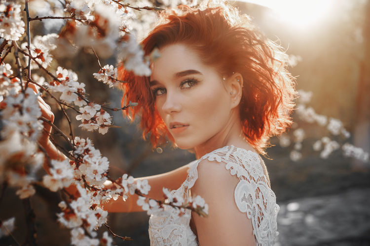 Portrait of beautiful redhead woman with white flowers