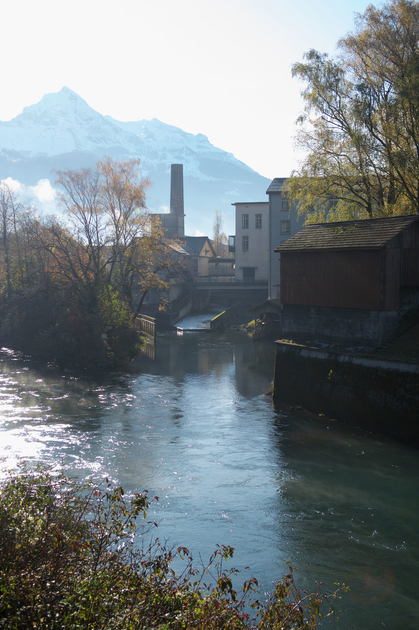 RIVER BY BUILDINGS AND MOUNTAINS AGAINST SKY