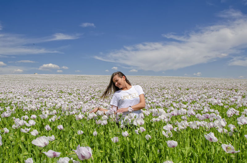 Woman with flowers on field against sky