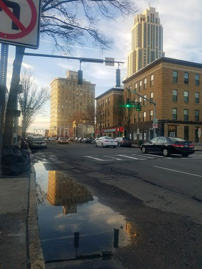 A beatiful puddle reflection in downtown New Rochelle, on North Avenue --- across the street from town pizza (3/23/2018) City Water Skyscraper Road Car Reflection Wet Sky Architecture Puddle Office Building Tall - High City Street Urban Skyline