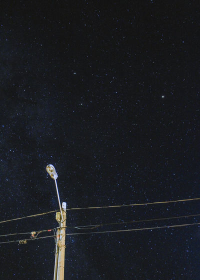 Low angle view of cables against sky at night