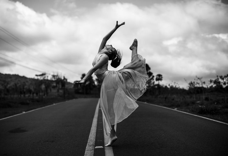Young woman dancing on road against sky