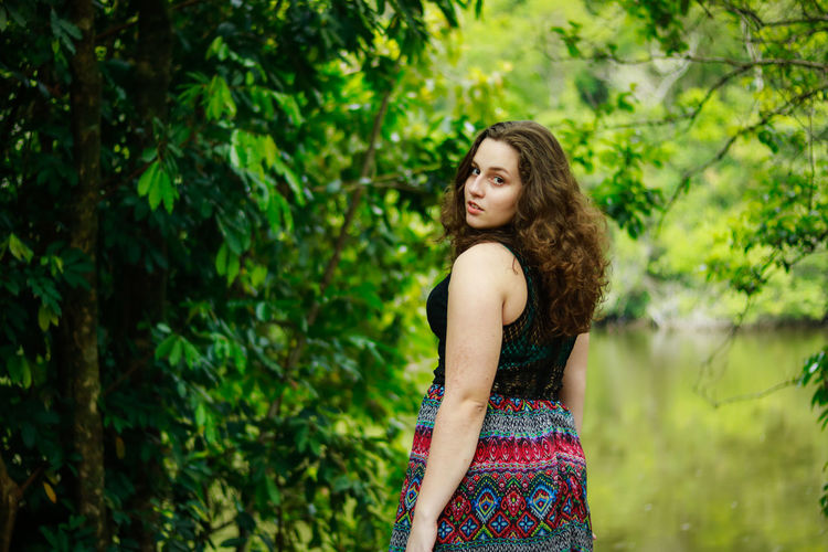Rear view portrait of teenage girl standing at park