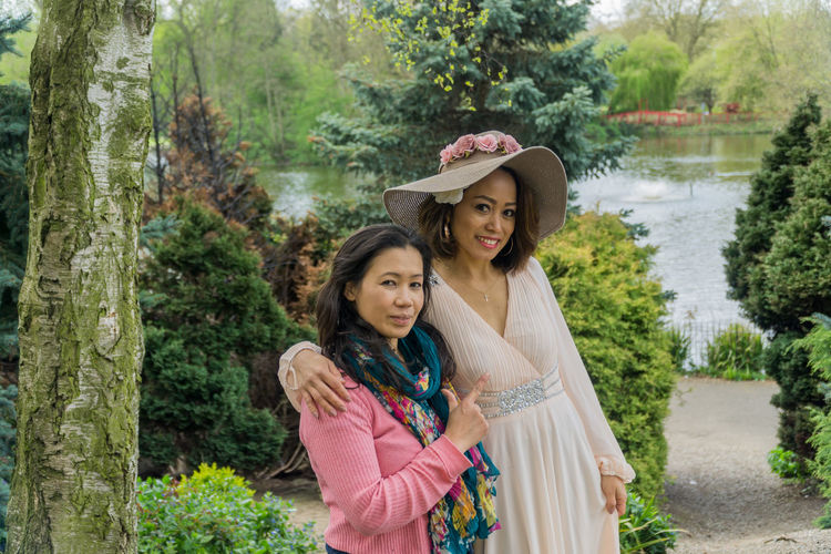 Two girl friends in a local park in the springtime. Asian Beauties Countryside Day Filipino Woman Girlfriends Lake Lush Foliage Models Outdoors Outside Park Pathway Tree Water Young Adults