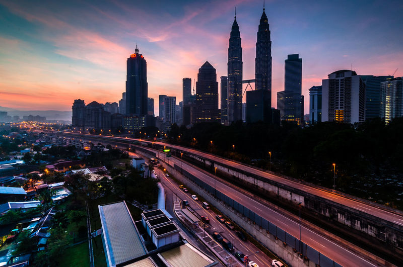 Petronas towers against sky during sunset in city