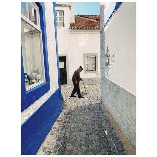 Full length of woman walking on street amidst buildings