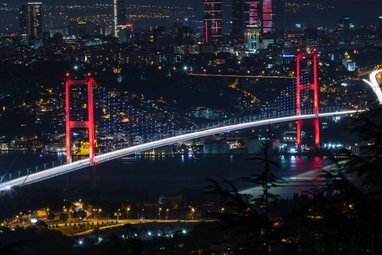 High angle view of illuminated bridge and buildings at night