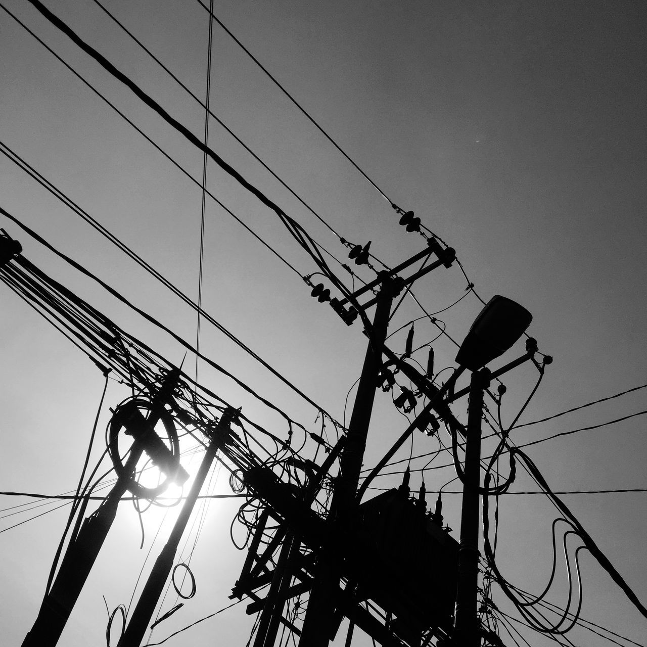 Low Angle View Of Silhouette Electricity Pylons Against Clear Sky