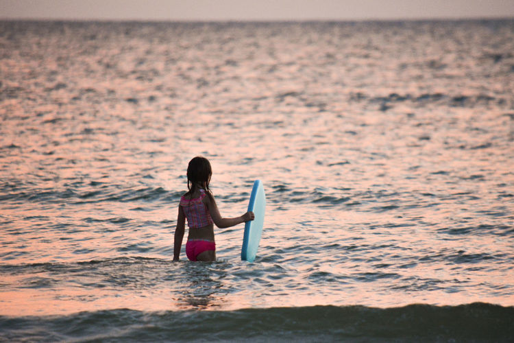 Rear view of woman standing in sea with surfboard