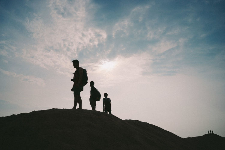 Low angle view of silhouette friends standing on rock formation against sky