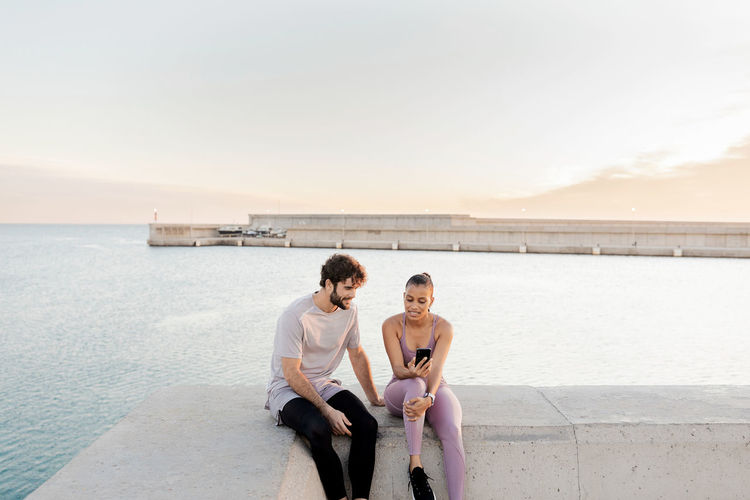 Friends sitting on sea shore against sky