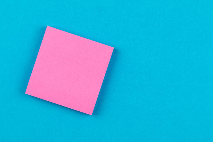 Directly above view of blank adhesive note on blue background