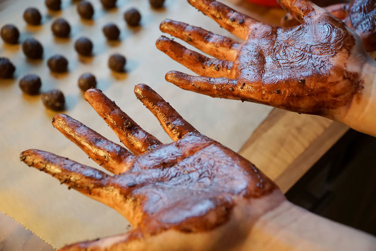Close-up of hands covered in chocolate