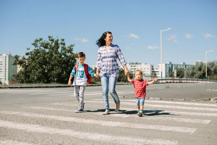 Mother And Children Walking On Zebra Crossing