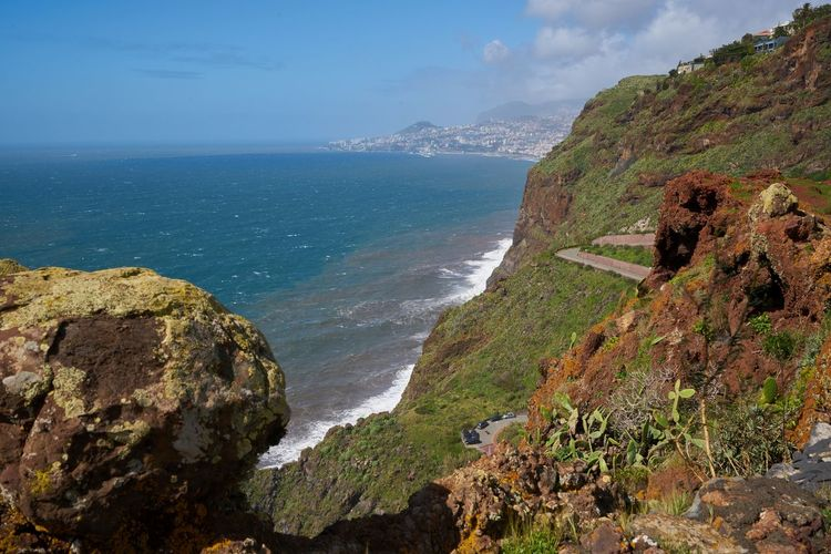 View of the coastline of Caniço, Madeira with Funchal city on the background Madeira Travel Island Portugal Portuguese Europe Landscape Nature Outdoors Aerial View Aerial Panorama Panoramic Rock Red Seascape Sea Ocean Atlantic Scenics Horizon Mountain Cost Coastline Shore