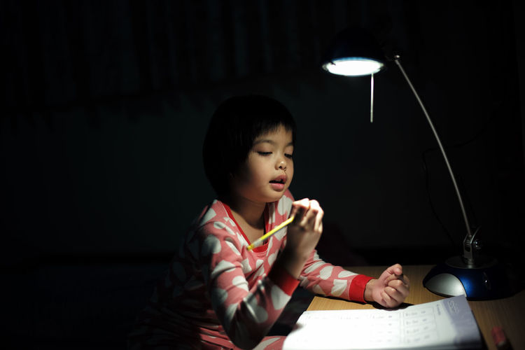 Cute girl studying at table with illuminated lamp in darkroom