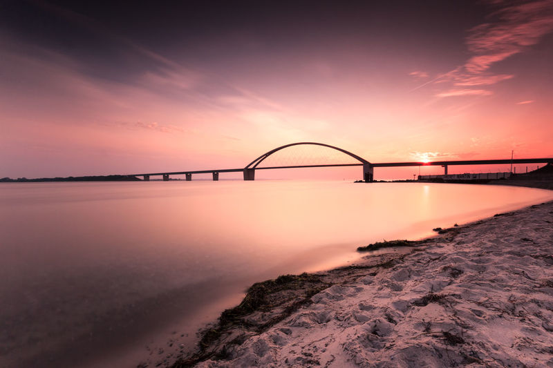 Sunset Sky Water Bridge Bridge - Man Made Structure Architecture Nature No People Connection Scenics - Nature Built Structure Sea Cloud - Sky Orange Color Travel Destinations Dramatic Sky Transportation Dusk Beauty In Nature Outdoors Fehmarn Fehmarnsundbrücke