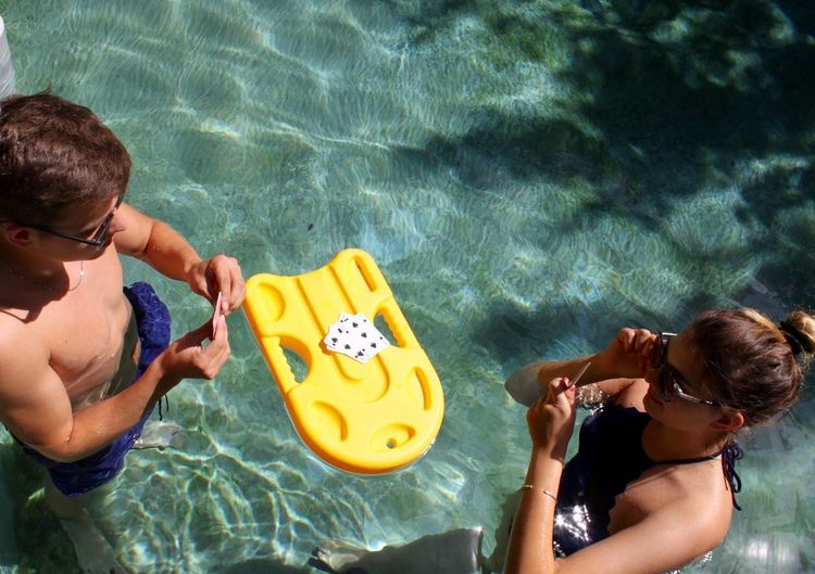 High Angle View Of Friends Playing Cards In Swimming Pool
