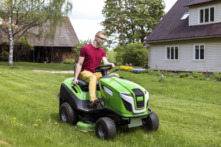 Young man, gardener driving ride on mower. Mowing grass in yard, tractor. Gardening. Architecture Building Building Exterior Countryside Day Front Or Back Yard Garden Gardener Grass Grass Grass Cutter Grass Cutting. House Lawn Lawnmower Mowing Tractor One Person Real People Riding Tractor Rural Rural Scene Tractor Tree