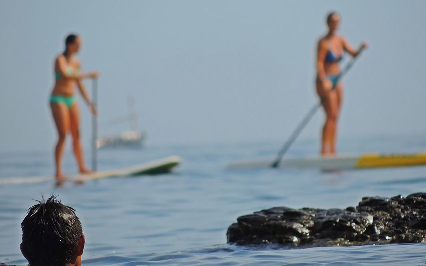 Rear view of man looking at women in biking paddleboarding on sea