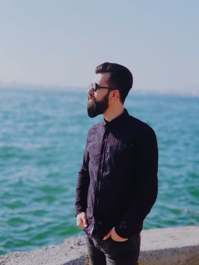 Handsome Man Standing At Beach Against Sky