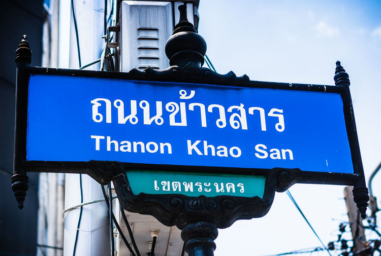 "Street sign sayin ""Thanon Khao San"" (Khao San Road), backpacker destination in Bangkok, Thailand. Architecture Bangkok Khao San Road Thai Thailand Wat Phra Kaew Blue Buddhism Communication Focus On Foreground Information Sign Landmark Low Angle View Nature No People Non-western Script Religion Road Sign Royal Palace Sign Text Travel Destinations"