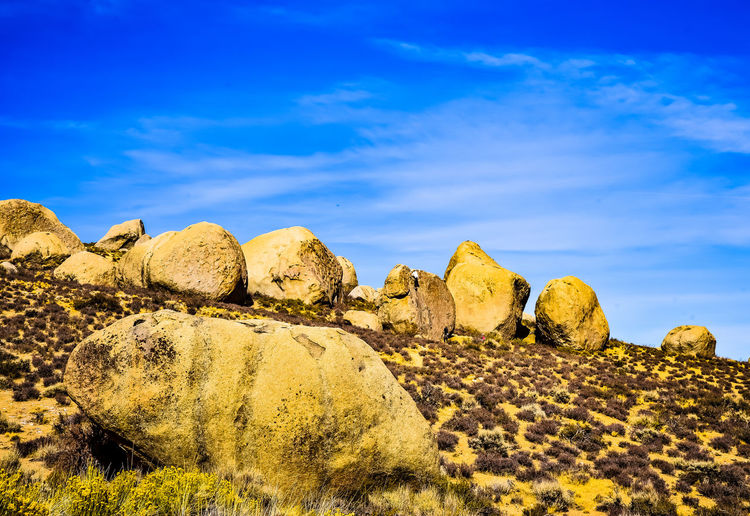 View of rocks on land against blue sky