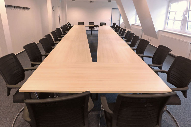 Empty chairs and table arranged in conference room