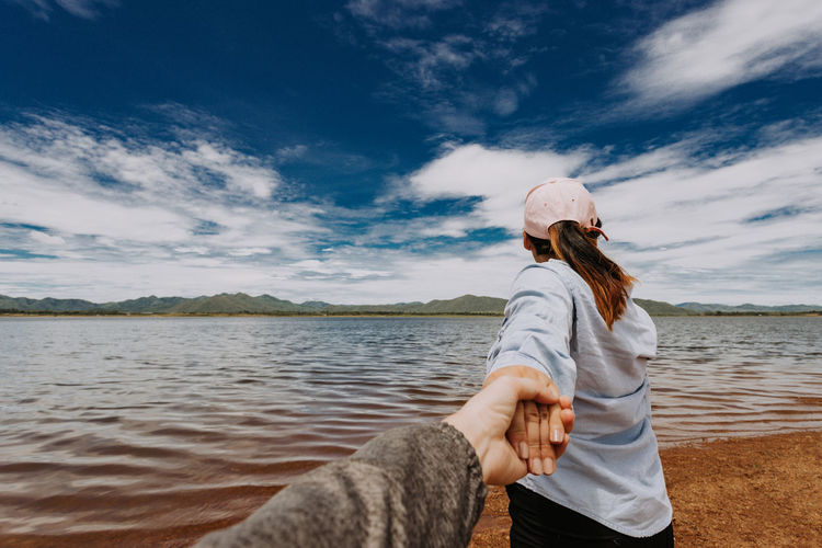 Woman holding man hands at beach against sky