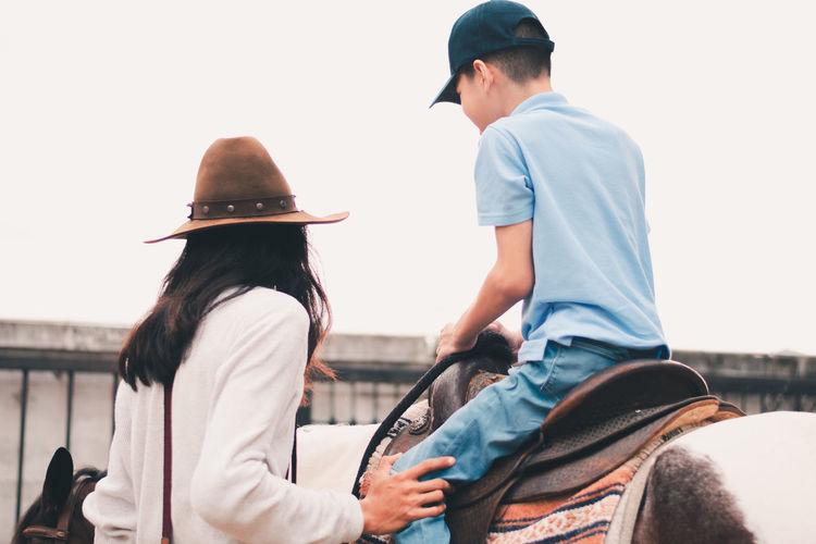 Boy sitting on horse with man standing by and looking away