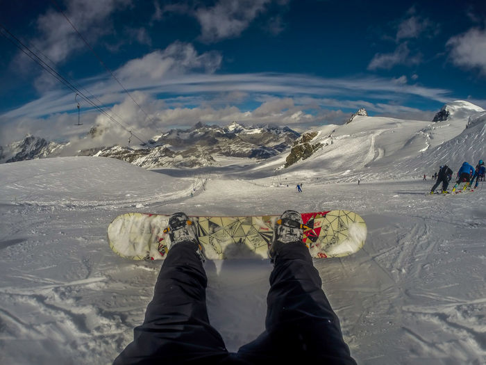 Low section of person snowboarding on snowcapped mountain