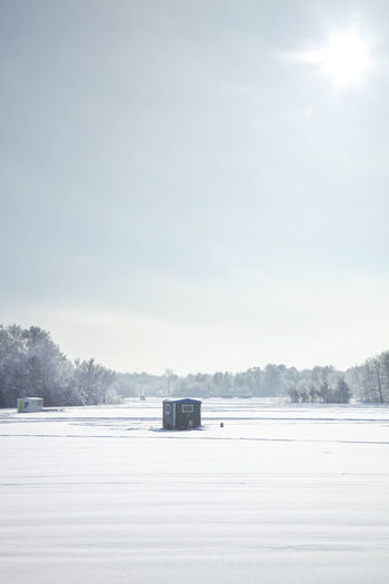 Hut on snow covered field against sky