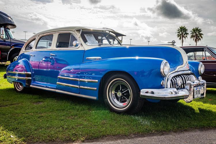 Vintage car parked on road against blue sky
