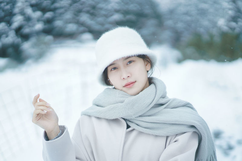 Portrait of young woman in park during winter