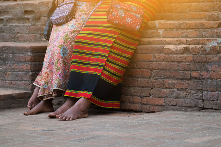 Sarong Adult Architecture Bagan barefoot Brick Brick Wall Built Structure Burmese Clothing Costume Cross Body Bag Day Daylight Human Body Part Lifestyles Low Section Myanmar Outdoors Real People Traditional Traditional Clothing Wall Women