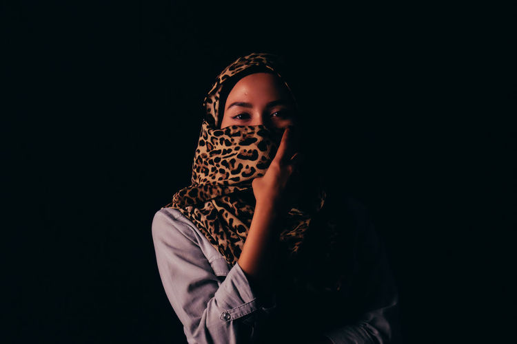 Portrait of young woman covering face with headscarf against black background