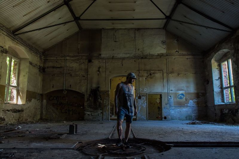 Full Length Of Man Standing In Abandoned Building