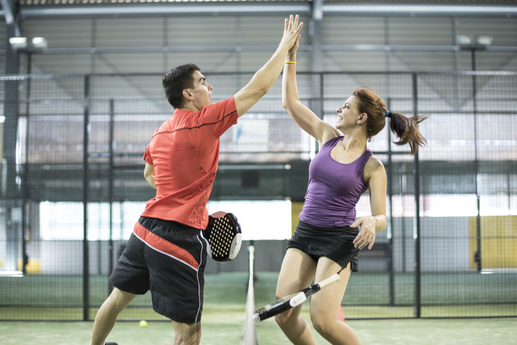Man and woman giving high five while playing paddle tennis