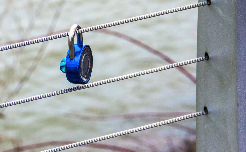 Locked up Metal Focus On Foreground Blue Hanging Safety Cable Outdoors Fence Railing Boundary Lock Bicycle Lock Blue Lock Metal Wire