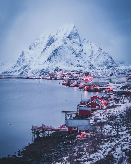 Scenic View Of Lake In Village By Snowcapped Mountain Against Sky